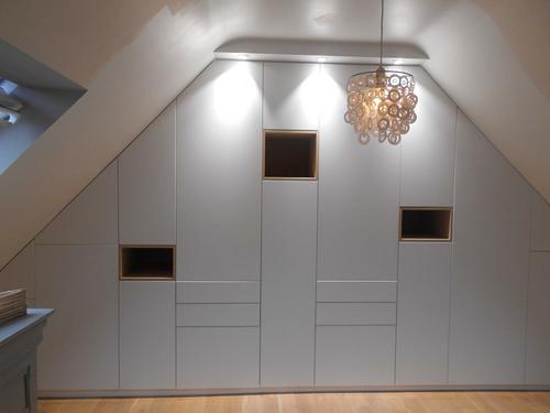 Aménagement placard laqué blanc sous combles avec portes et tiroirs